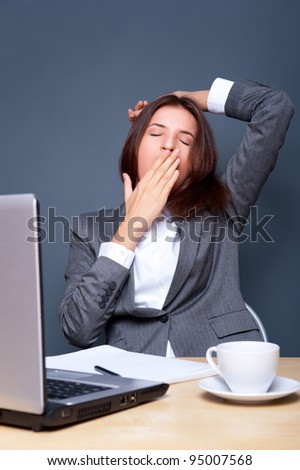 Bored businesspeople: woman sitting at desk with closed eyes. Young caucasian business woman at her office. - stock photo