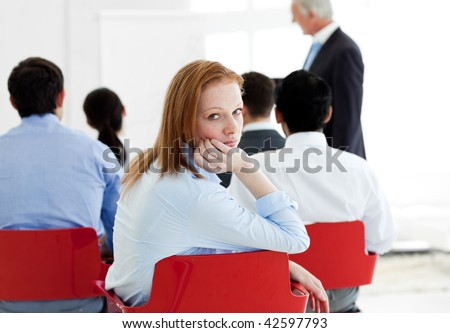 Bored businesswoman at a conference with her colleagues - stock photo