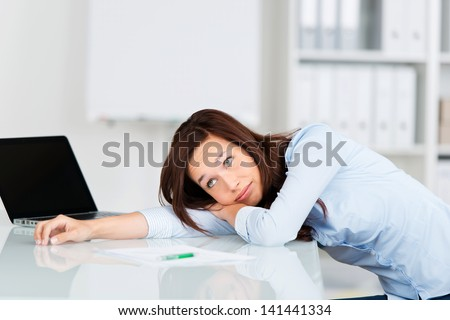 Bored businesswoman relaxing in her chair with her head lying on the desk - stock photo