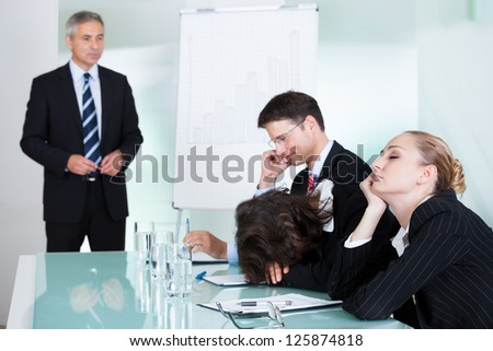 Bored businesswoman sleeping in a meeting as her colleague who is giving the presentation talks in the background