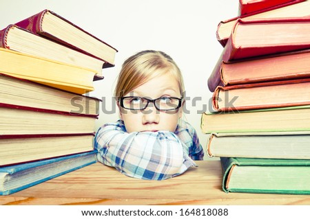 Bored child with a stack of books - stock photo