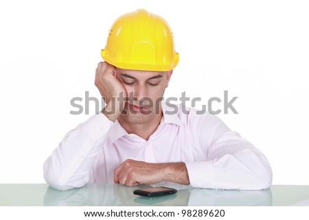 bored craftsman looking at his phone - stock photo