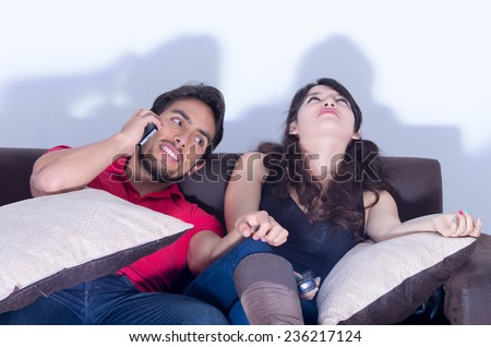 bored girlfriend watching television while boyfriend chats on the phone - stock photo
