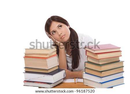 bored High school or college Latina female student sitting by the desk with pile of books in front of her - stock photo