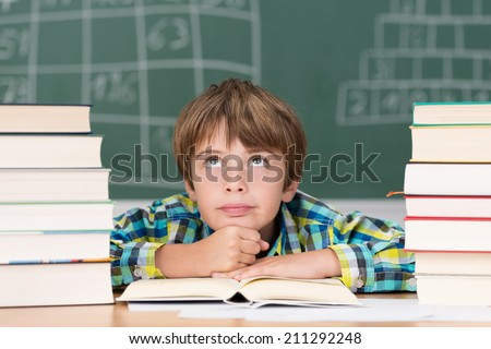 Bored little boy in the school room sitting staring up into the air daydreaming flanked by two tall stacks of textbooks