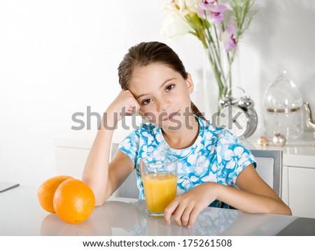 bored little girl with orange juice - stock photo