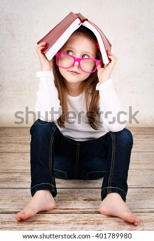 Bored little schoolgirl wearing glasses and hiding in the book - stock photo