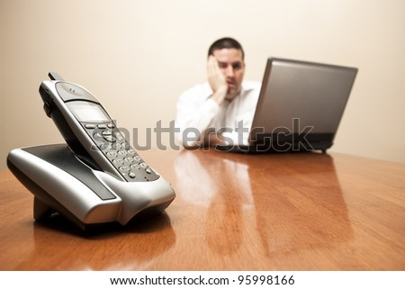 Bored man sitting at laptop waiting for a call - stock photo