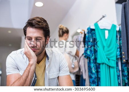 Bored man sitting in front of his girlfriend in clothing store - stock photo