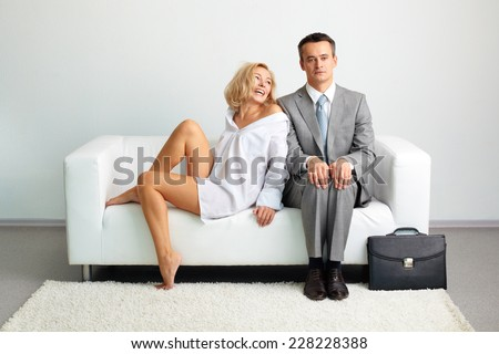 Bored man sitting on sofa with laughing woman looking at him near by - stock photo