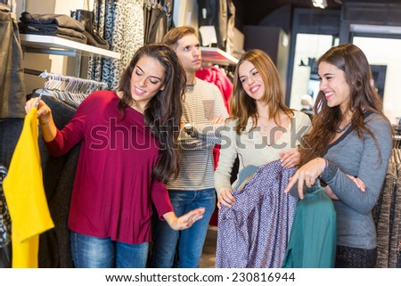 Bored Man Waiting for Women in a Clothing Store. The man is on Background with crossed arms, Women are in foreground and they don't seem to take care of him - stock photo