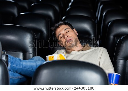 Bored mid adult man sleeping at cinema theater - stock photo