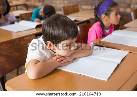 Bored pupil sitting at his desk at the elementary school - stock photo