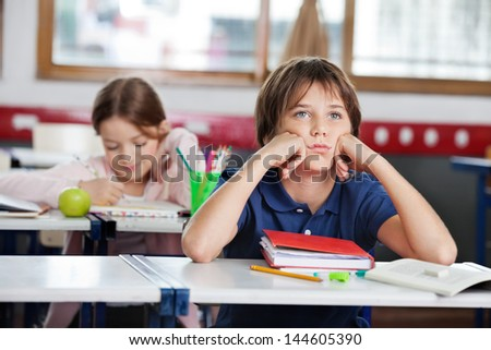 Bored schoolboy looking away while sitting at desk with girl in background at classroom - stock photo
