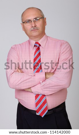 Bored senior businessman in a shirt with hands folded isolated on grey - stock photo