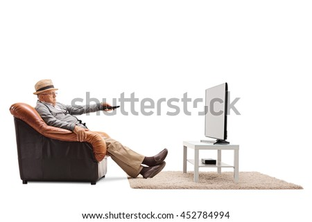 Bored senior changing channels on his TV seated on an armchair isolated on white background