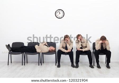 Bored, stressed and exhausted people sitting on chairs waiting - stock photo