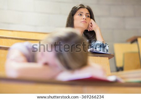 Bored student listening while classmate sleeping in university - stock photo
