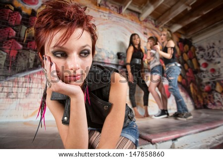Bored teen with chin in hands near group - stock photo