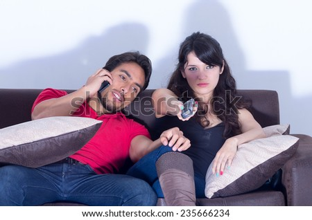 bored tired girlfriend watching television while boyfriend chats on the phone - stock photo