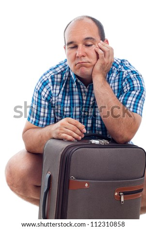 Bored traveller tourist man waiting with luggage, isolated on white background. - stock photo
