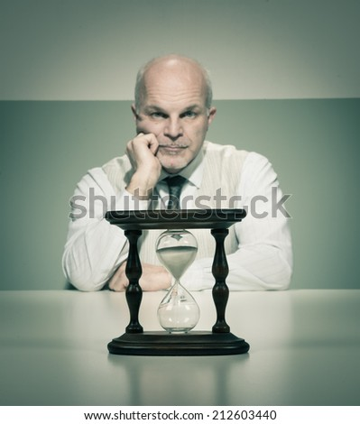 Bored vintage businessman waiting at desk with hourglass. - stock photo