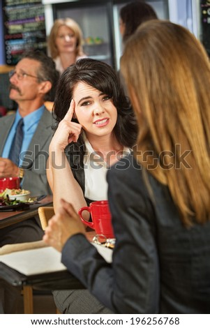 Bored woman with coworker in coffee house