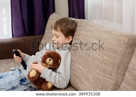Bored 7 year old boy child sitting on the sofa and watching tv. Hugs his favorite teddy bear and changing channels by remote control. - stock photo