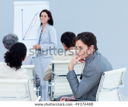 Bored young businessman at a presentation with his colleagues - stock photo