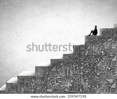 Bored young businesswoman sitting alone on ladder steps - stock photo