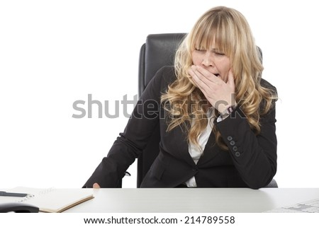 Bored young businesswoman yawning as she waits for the end of her working day at the office, on white - stock photo