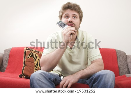 Bored young man is watching TV - stock photo