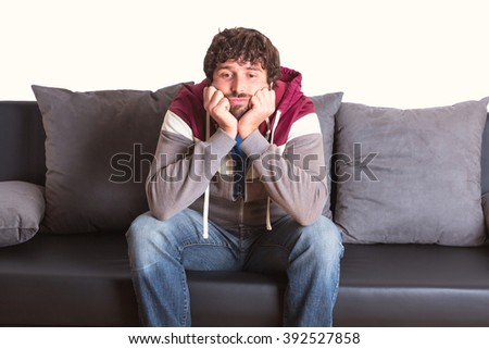 bored young man sitting at home on sofa  - stock photo
