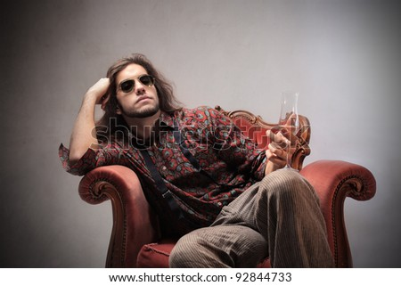 Bored young man sitting on an armchair and holding a glass of champagne