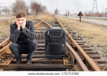 Bored young man waiting for a delayed train crouching down in the centre of a rural railway line on the wooden sleepers with his chin in his hands and his luggage alongside - stock photo