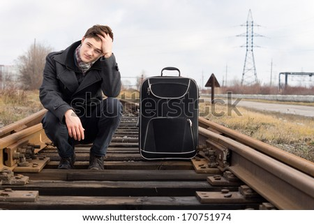Bored young man waiting for the arrival of a train squatting on the sleepers in the centre of the railway line with his head on his hand and his suitcase alongside - stock photo