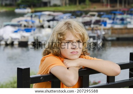 bored young teen is sitting at the docks with nothing to do - stock photo
