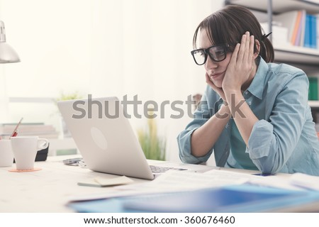Bored young woman in the office working with a laptop and staring at computer screen - stock photo