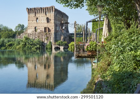 BORGHETTO, ITALY - JULY 11: Ruin of tower at Visconteo bridge, framed by vegetation and coasted by river Mincio. July 11, 2015 in Borghetto. - stock photo