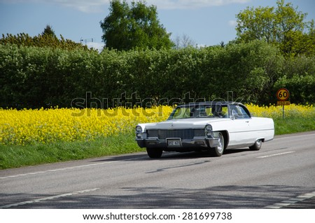 BORGHOLM, SWEDEN - MAY 23, 2015: Old timer car  Cadillac de Ville, 1965, on the road heading for a car meeting in the town of Borgholm in Sweden, Photo is taken on May 23, 2015, at Oland in Sweden. - stock photo