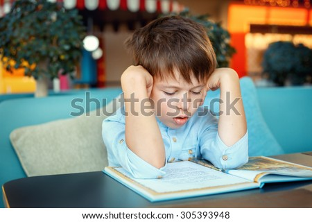 Boring and tired little boy reading book for elementary school - stock photo