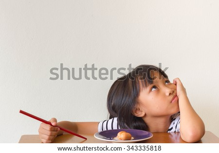Boring asian children girl with food and red chopsticks sitting at the table