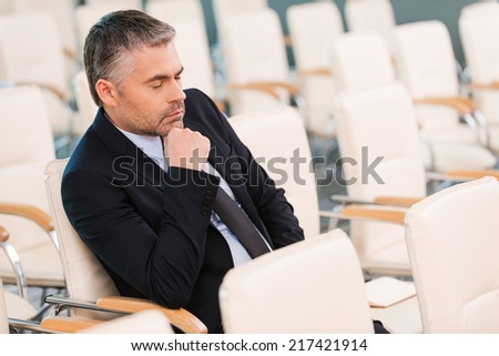 Boring conference. Bored mature man in formalwear holding hand on chin and keeping eyes closed while sitting on the chair in empty conference hall  - stock photo