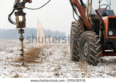 boring holes in ground with drilling rig during fence construction - stock photo