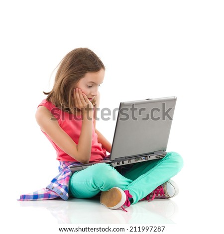 Boring homework on a laptop. Little girl sitting on the floor with legs crossed, reading something on the laptop and looking bored.