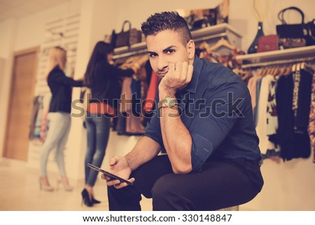 Boring man in shopping store. Women buying in background