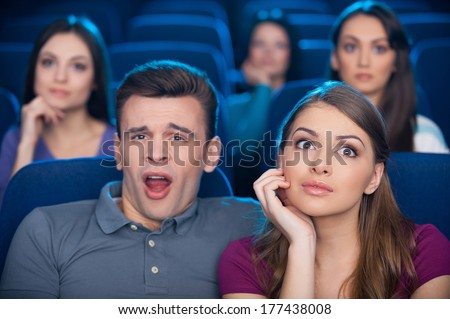 Boring movie? Bored young man sitting close to his excited woman while watching movie at the cinema - stock photo