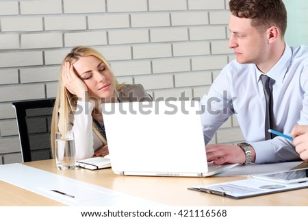 people bored at work. boring work. young business people looking bored while sitting together at the table and work d