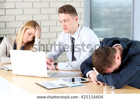 Boring work. Young business people looking bored while sitting together at the table and looking away - stock photo