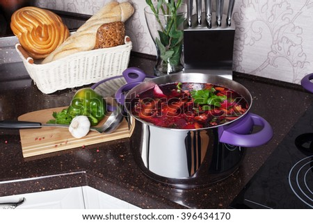 borscht soup wooden board knife kitchen countertops, interior, pan hob cooker, cooking Interior atmosphere, domesticity, cooking process - stock photo